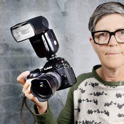 photo of Marlene holding camera with flash mounted on top