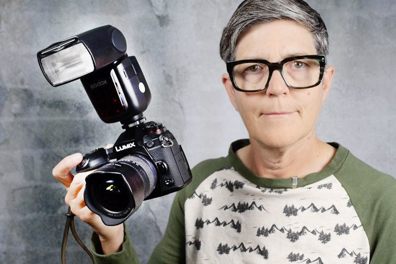 Photo of Marlene holding her camera with a flash mounted on top